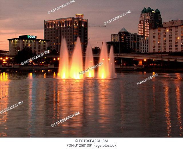 Orlando, FL, Florida, Downtown skyline, Lake Lucerne, illuminated fountain, evening