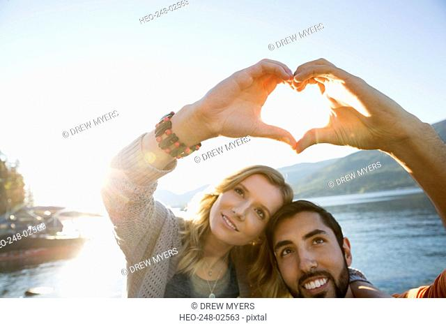 Young couple forming heart-shape with hands lakeside