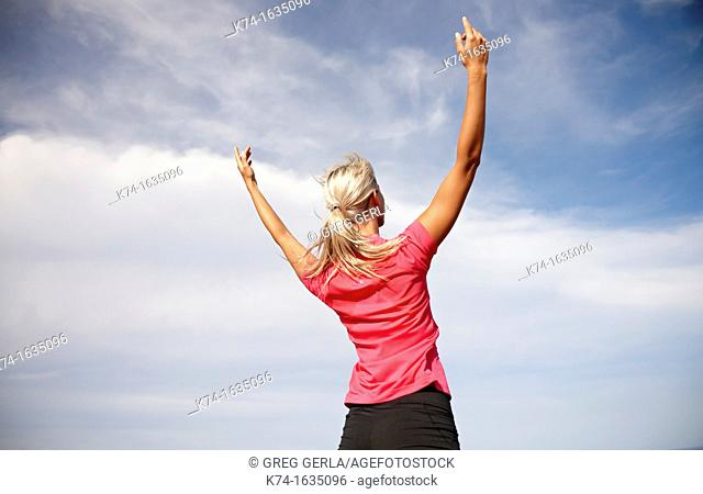 Woman with arms raised in the air
