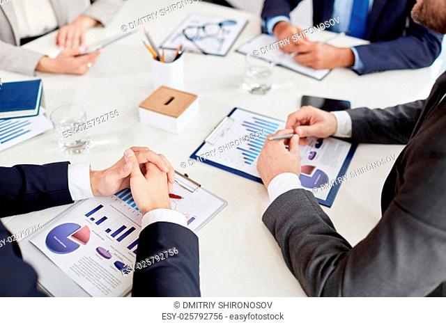 Hands of employee on business paper at workplace during meeting