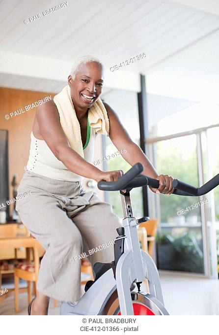 Older woman using exercise bike in home