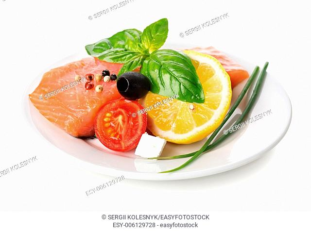 Salmon fillet with vegetables and lemon in plate isolated on white