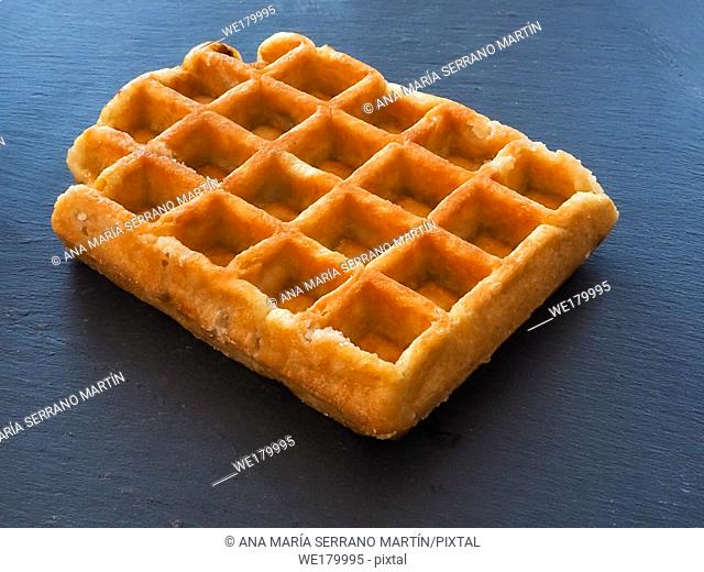 A Belgian waffle on a slate plate