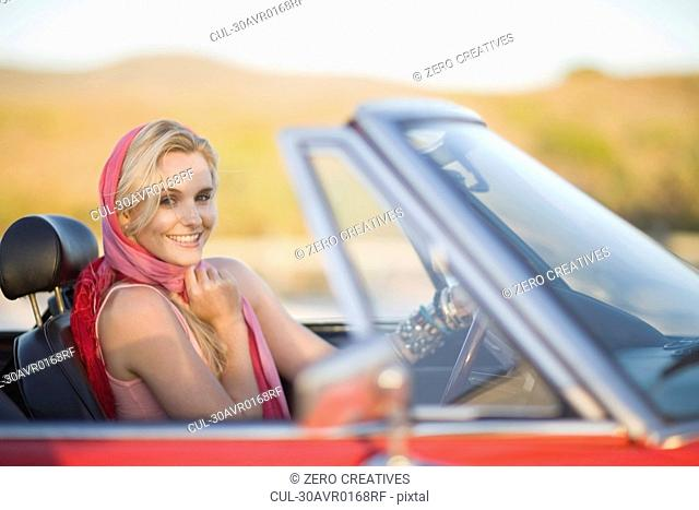 Blond woman with red scarf in cabriolet