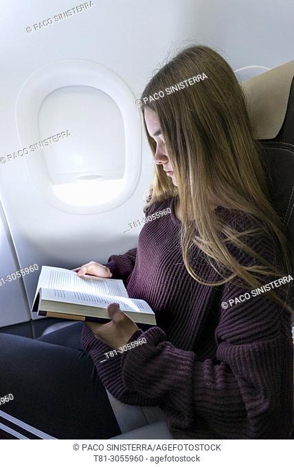 Girl reading book inside airliner
