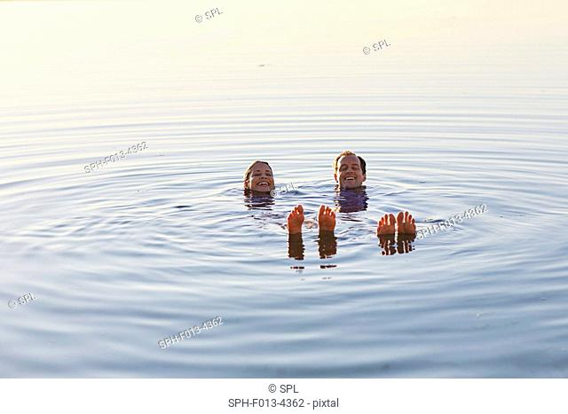 MODEL RELEASED. Couple floating in the sea