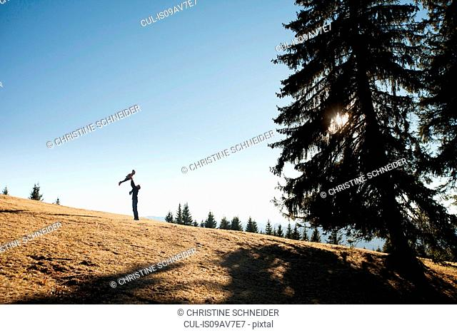 Silhouette of man holding up toddler daughter on hill, Tegernsee, Bavaria, Germany