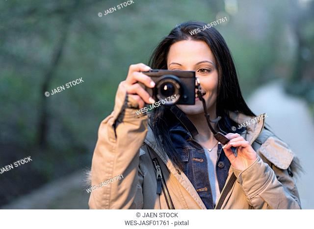 Smiling young woman holding camera outdoors