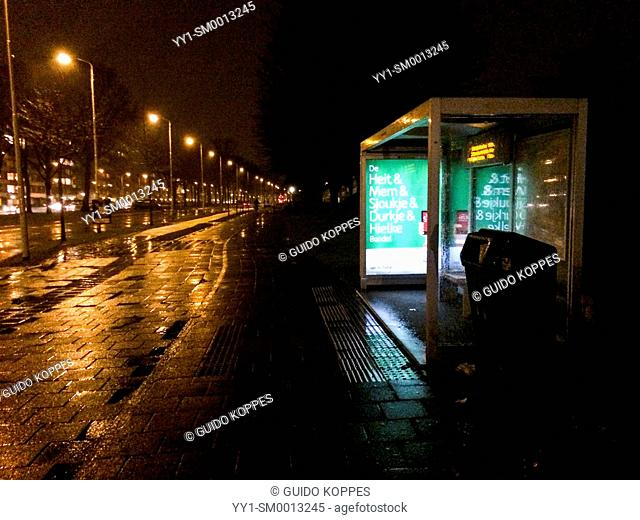 Eindhoven, Netherlands. Empty street with bus stop but without traffic, lit by street lanterns, during a rainy, winter night