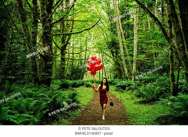 Korean woman holding red balloons in lush forest