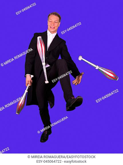 Elegant and happy man juggling with three juggling clubs