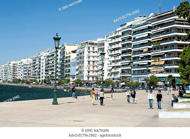 View of buildings on Nikis Avenue and pedestrians strolling on the waterfront in Thessaloniki, Greece