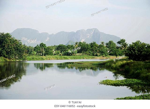 View landscape of fishing lift and dip net machine in canal at Ban Pak Pra fishing village and Khao Oktalu Mountain or The Hole Mountain in Phatthalung province...