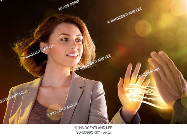 Young woman touching light streams, connecting to another person