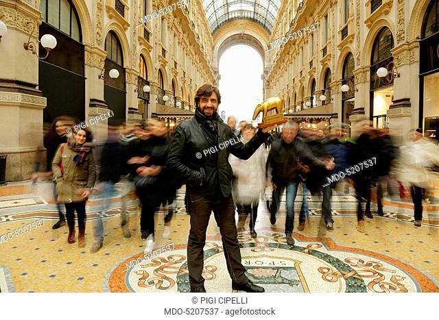 TV personality Valerio Staffelli posing with the Tapiro d'Oro (Golden Tapir) in his hand, in Galleria Vittorio Emanuele II. Milan, Italy