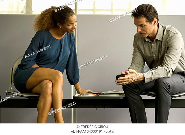 Professionals chatting in waiting room, man showing woman smartphone
