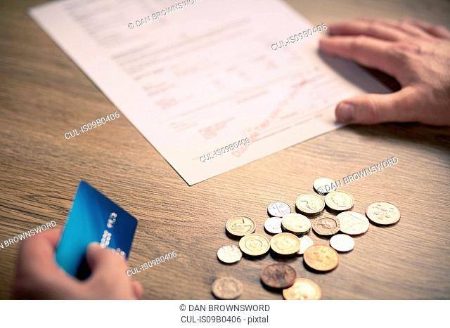 Mans hands holding credit card with coins and bill on table