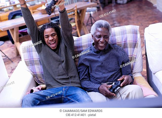 Enthusiastic grandfather and grandson playing video game on sofa