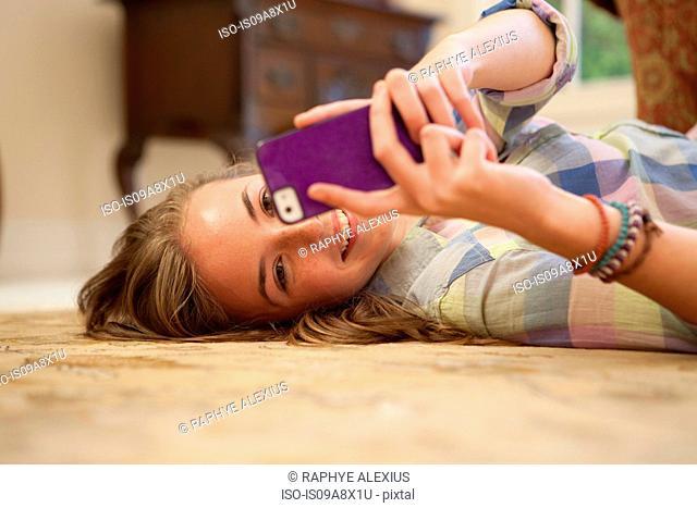 Teenage girl lying on floor with cell phone