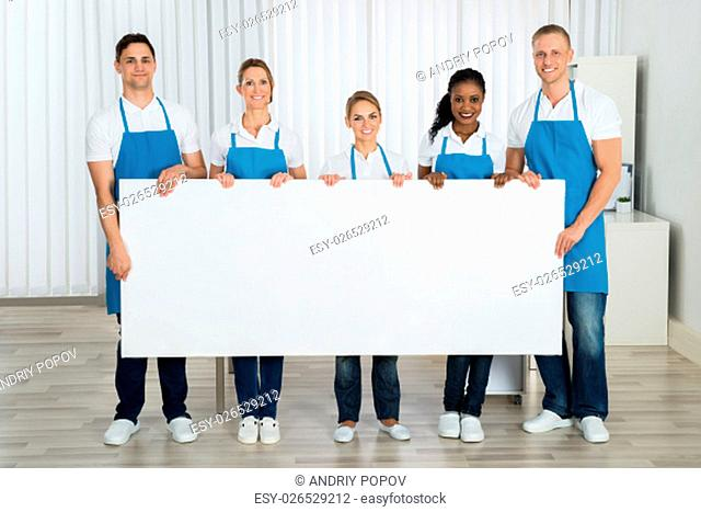 Group Of Happy Cleaners In Uniform Holding Blank Banner In Office