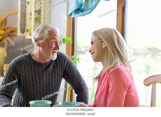 Mature couple gazing at each other in dining room
