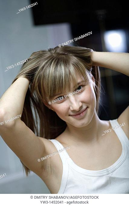 headshot of the pretty blond women weared tank top indoors smiling with heands in hairs Caucasian, 24 years old