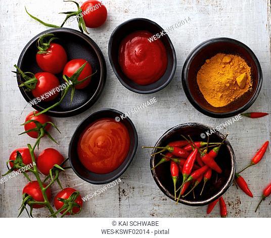 Tomatoes, red chili, curry powder, chili ketchup, curcuma and tomato ketchup in bowls
