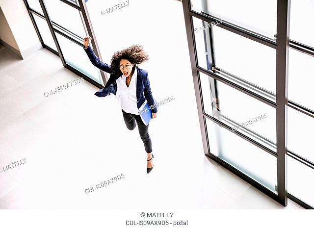 High angle view of businesswoman running through office entrance