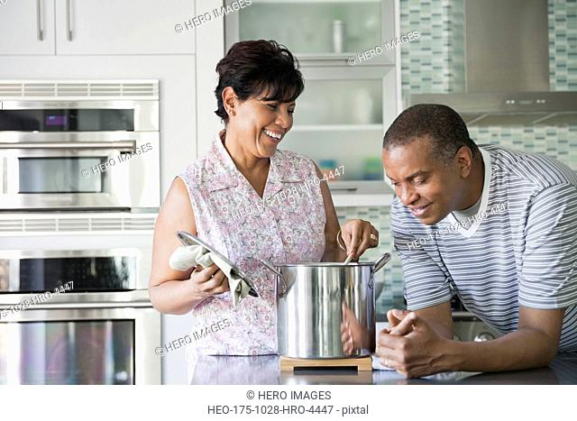 Mature man looking in cooking pot while wife stirs