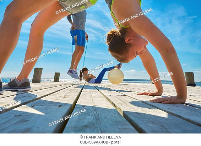 Friends on pier using exercise equipment