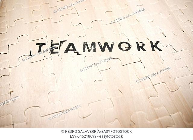 Teamwork word stamped on a wooden puzzle