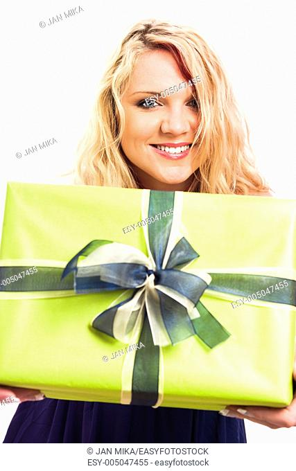 Young blond happy woman holding green gift box, isolated on white background