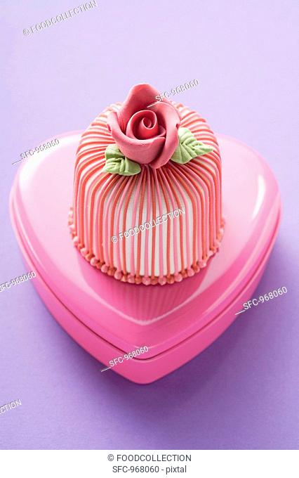 Marzipan-covered cake on pink chocolate box