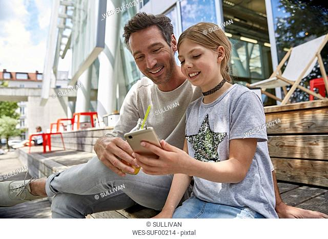 Happy father and daughter looking at cell phone at an outdoor cafe