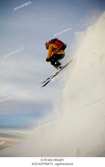 A male backcountry skier drops a cliff while out ski touring, Sol Mountain, Monashee Backcountry, Revelstoke, BC