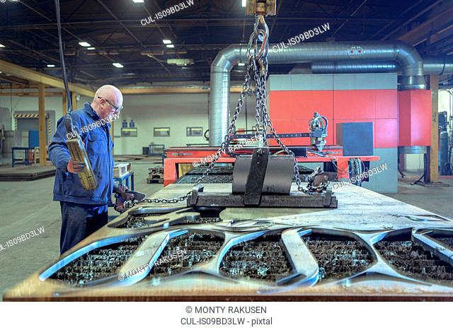 Worker with plasma cutter machine with steel offcuts in engineering factory