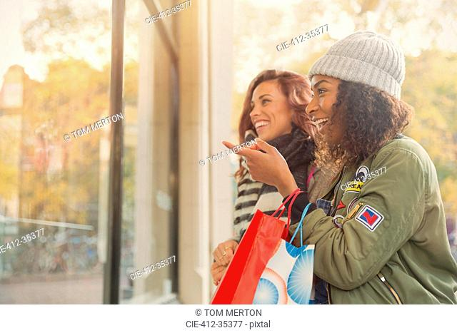 Young women friends window shopping at storefront