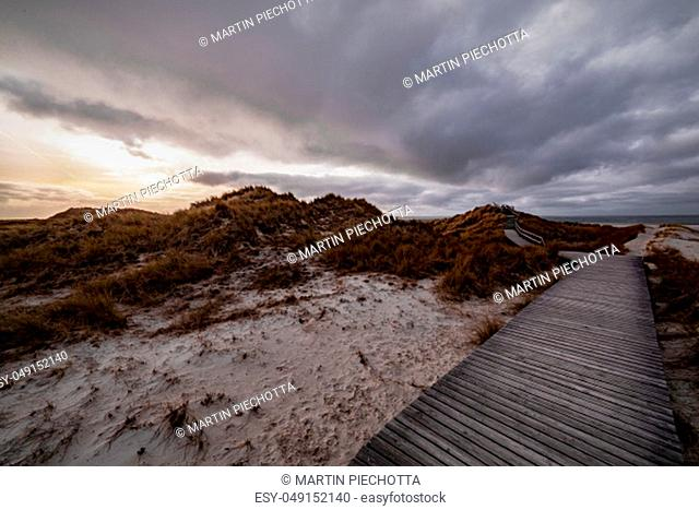 Deserted wooden boardwalk leading away through coastal dunes vegetation towards a glowing cloudy sunset sky in a moody evening landscape on Amrum