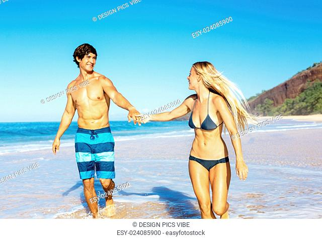 Happy Attractive Couple Playing and Having Fun on Beautiful Sunny Beach