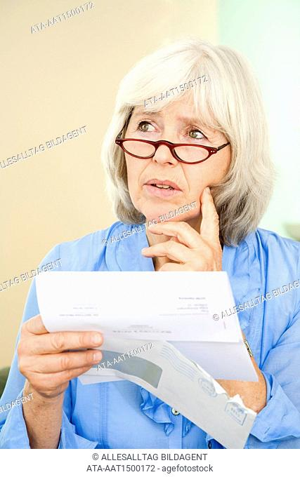 Elderly lady reading an official letter