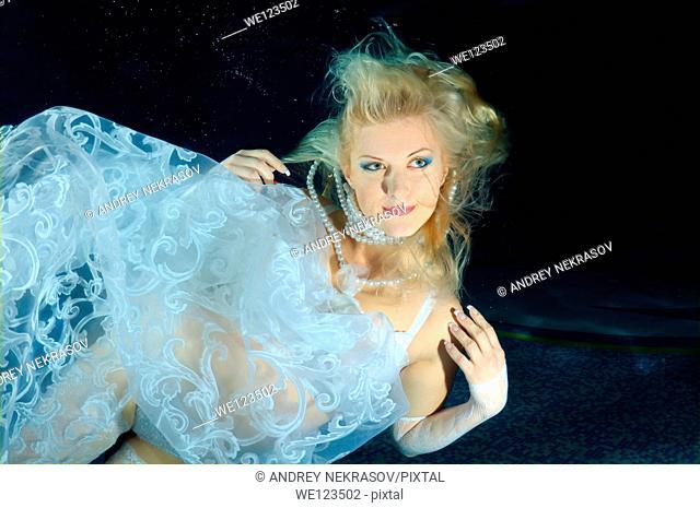 Woman, underwater model presenting fashion in pool