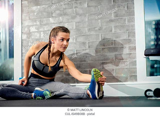 Young woman training, touching toes in gym