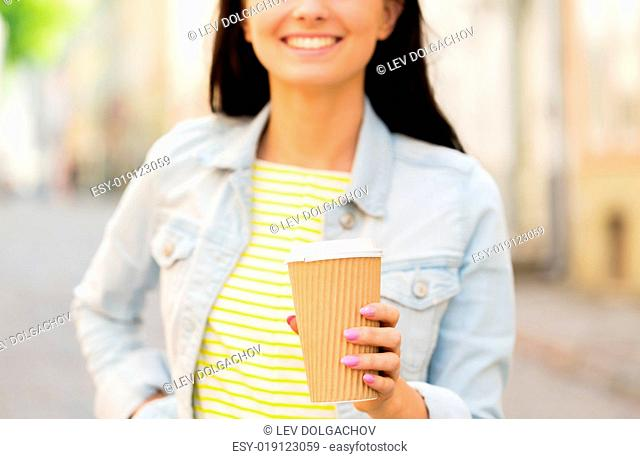 vacation, weekend, takeaway drinks, leisure and friendship concept - close up of happy young woman or teenage girl drinking coffee from disposable paper cups on...