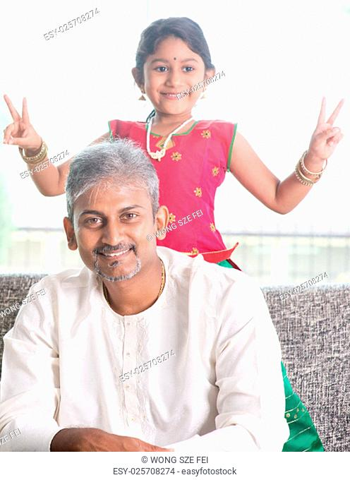 Happy Indian family at home. Asian girl showing peace hand sign. Adults and kids indoor lifestyle