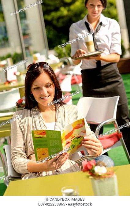 Woman checking menu waitress bringing order coffee