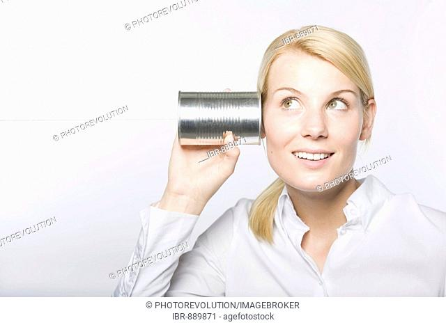 Young blonde woman holding a tin can telephone to her ear