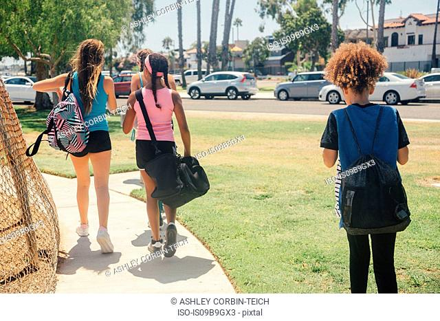 Schoolgirls walking to soccer practice on school sports field