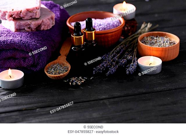 Lavender oil with soap, salt and flowers on black wooden table