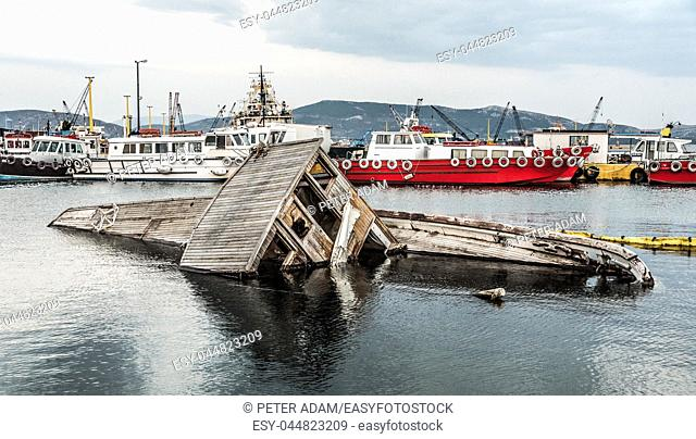 Sinking wooden boat at the harbor in Greece