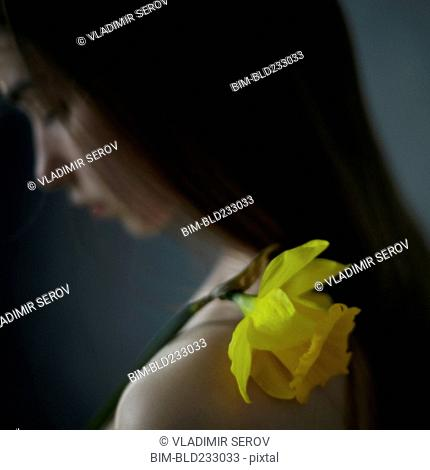 Caucasian girl with yellow flower on shoulder